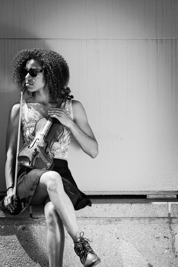 Gafas de sol de la mujer afroamericana y violín el sostenerse que llevan fotos de archivo