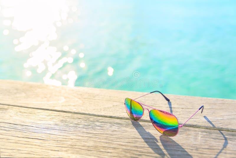 Gafas de sol del arco iris que mienten en un decking de madera fotos de archivo