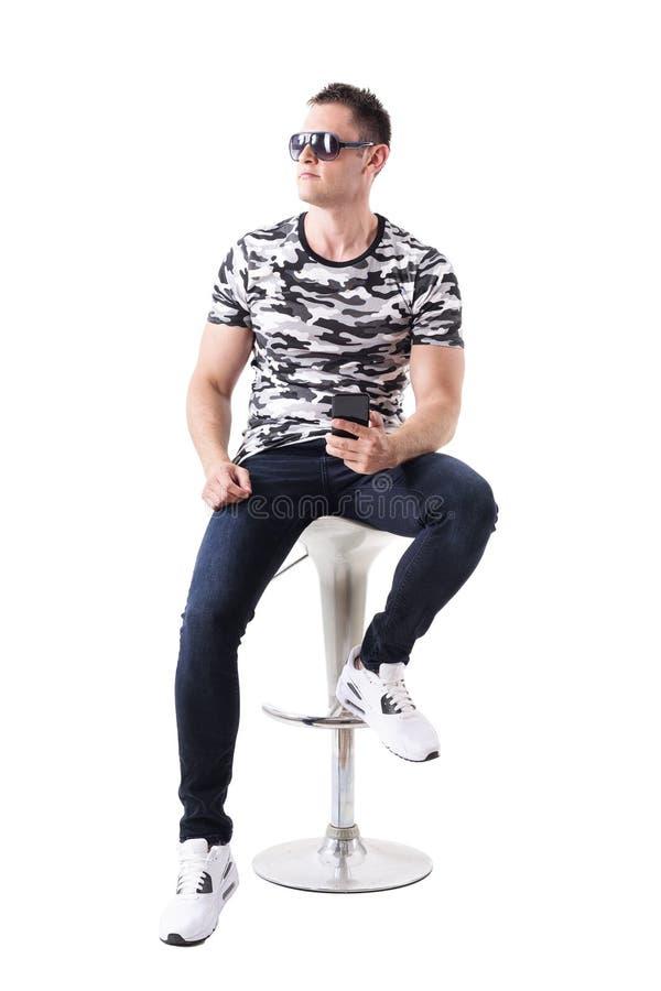 Gafas de sol del hombre fresco y camiseta del camuflaje que llevan que sostiene el teléfono móvil que mira la sentada ausente en  fotos de archivo