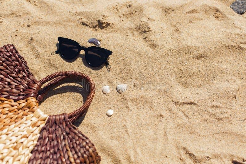 Gafas de sol elegantes, bolso de la paja en la playa arenosa con las conchas marinas, visión superior con el espacio de la copia  imagenes de archivo