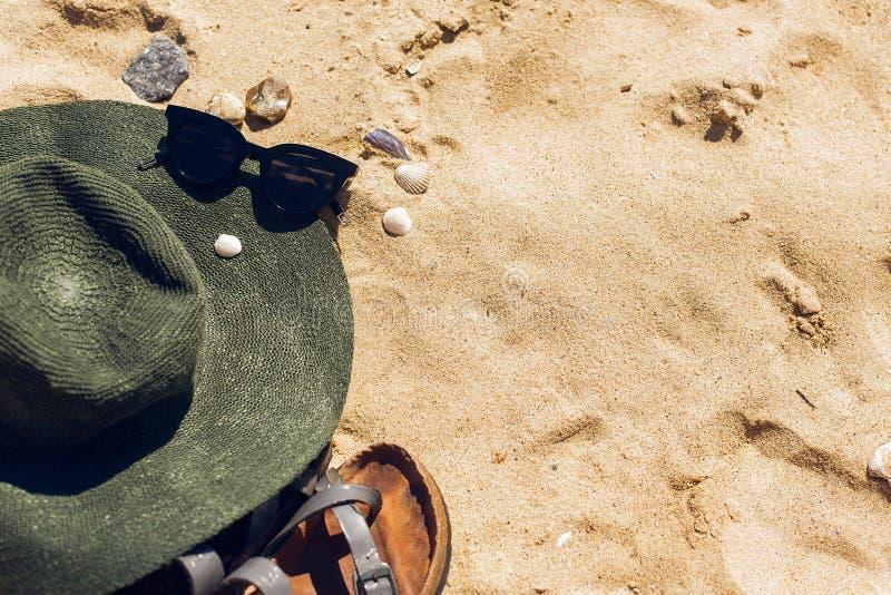 Gafas de sol elegantes, sombrero, sandalias en la playa arenosa con las conchas marinas, visión superior con el espacio de la cop imagen de archivo libre de regalías
