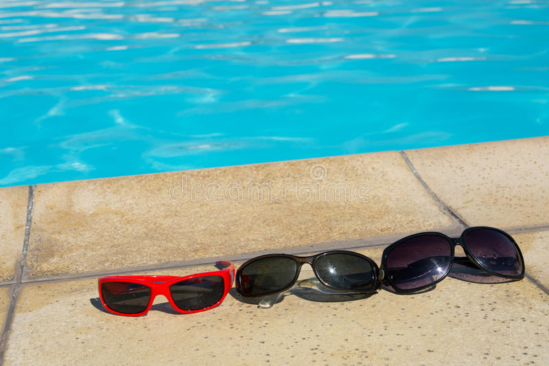 Gafas de sol en el borde de la piscina imagen de archivo