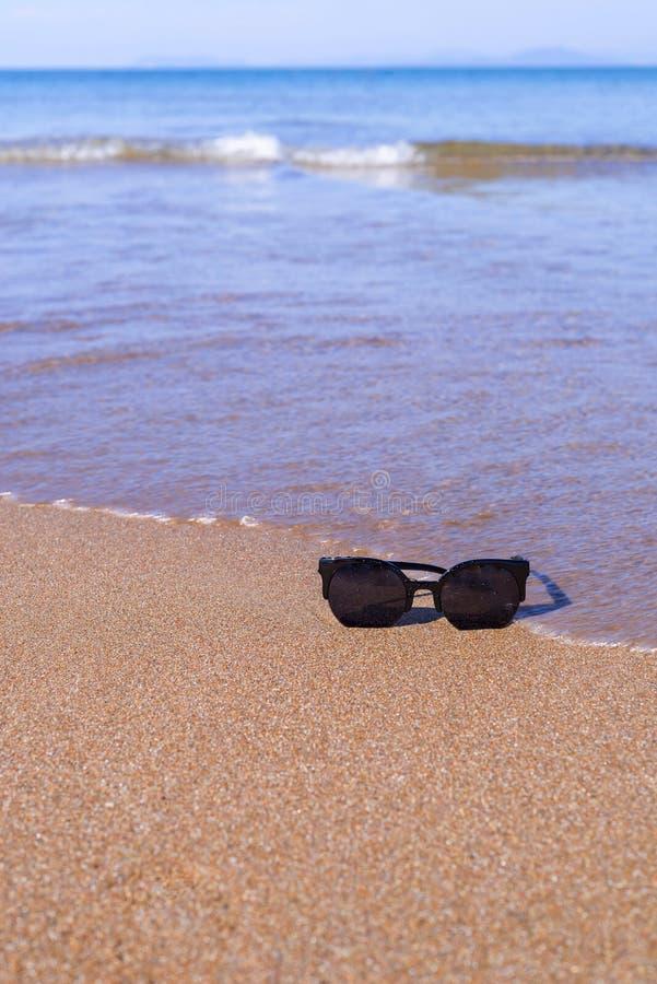 Gafas de sol en el primer de la costa de mar fotos de archivo