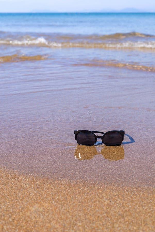 Gafas de sol en el primer de la costa de mar imagenes de archivo