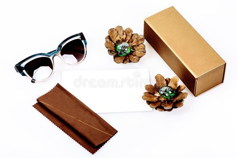 Gafas de sol en la composición con una caja y un paño en un fondo blanco imagenes de archivo