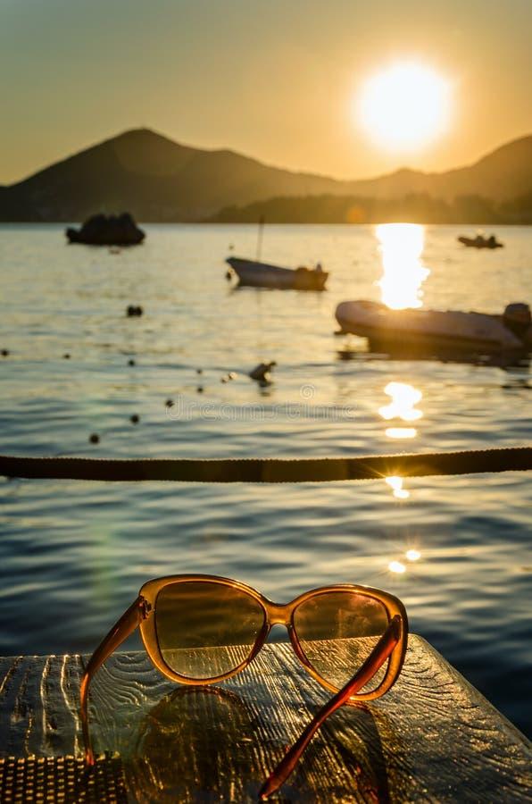 Gafas de sol en la tabla de madera en la puesta del sol fotografía de archivo libre de regalías