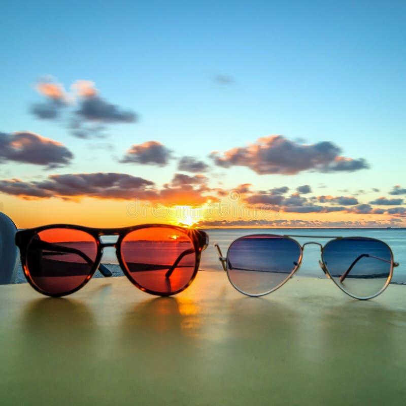 Gafas de sol en la tabla tropical de la playa en la puesta del sol fotos de archivo libres de regalías