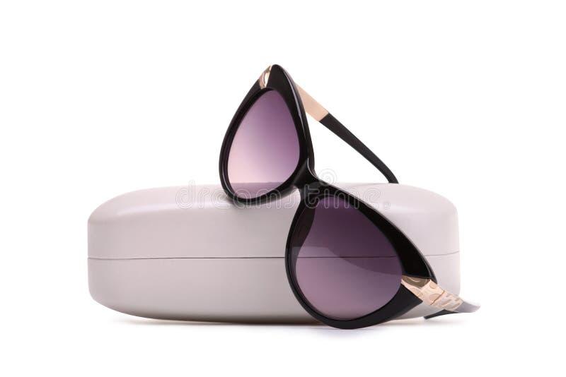 Gafas de sol en un caso del almacenamiento en un fondo blanco imágenes de archivo libres de regalías