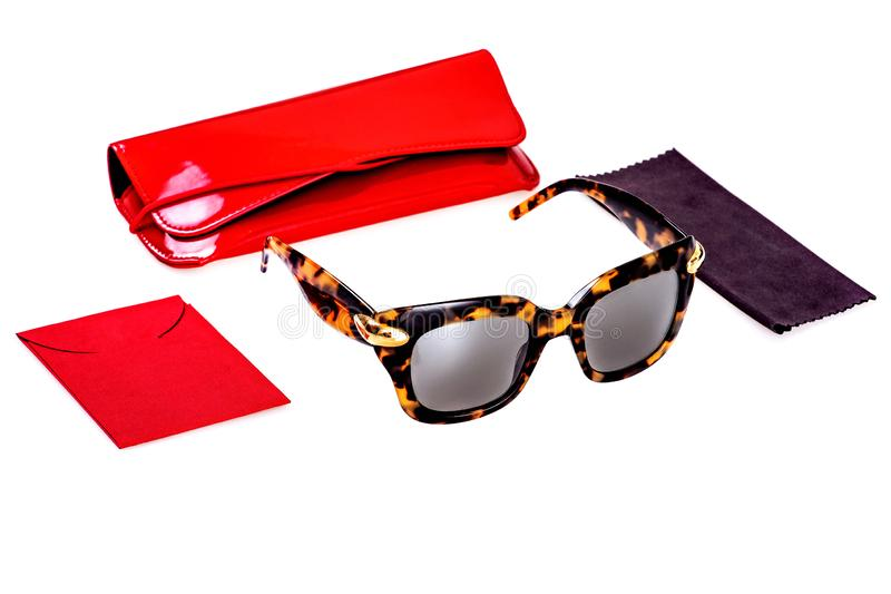 Gafas de sol en un marco negro y amarillo plástico conjuntamente con una caja roja, una caja y un trapo en un fondo blanco imagen de archivo libre de regalías