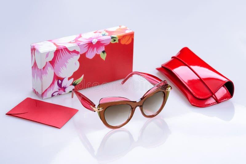 Gafas de sol en un marco, una caja, una bolsa y un sobre modernos en un fondo brillante blanco con la reflexión foto de archivo libre de regalías