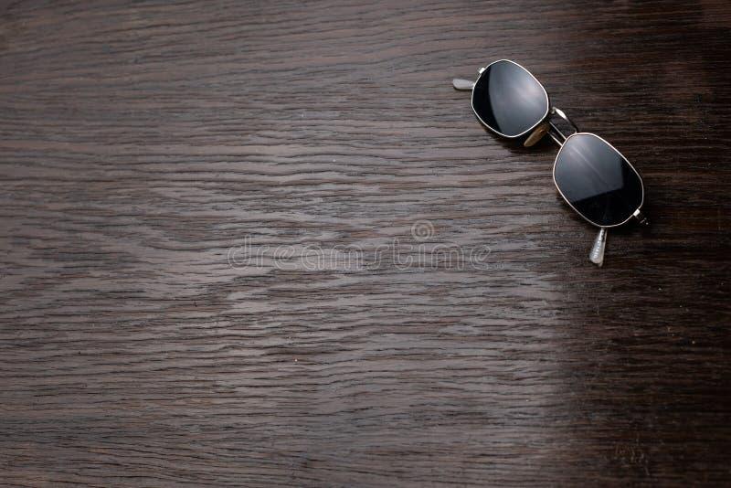 Gafas de sol en una tabla de madera oscura imagen de archivo