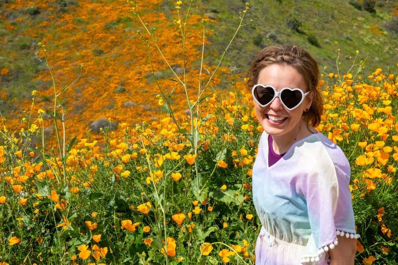 Gafas de sol hermosas del corazón de la mujer que llevan joven y un caftán en colores pastel en un campo de la amapola durante la imágenes de archivo libres de regalías
