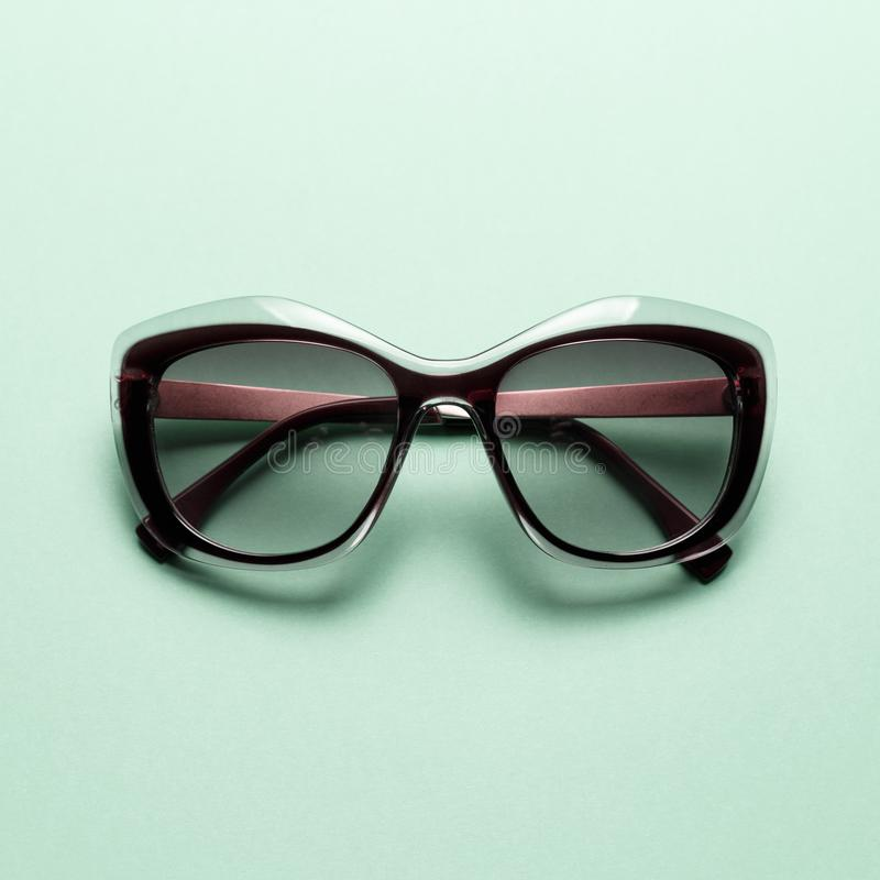 Gafas de sol de la moda en fondo de la menta fotos de archivo