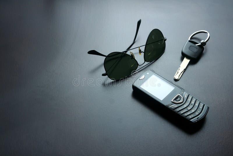 Gafas de sol, llave del coche y teléfono móvil en una tabla de madera imagen de archivo