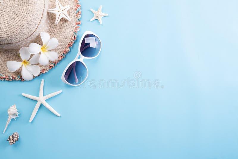 Gafas de sol de los accesorios de la playa, sombrero de la playa de las estrellas de mar y cáscara del mar en el fondo en colores fotografía de archivo
