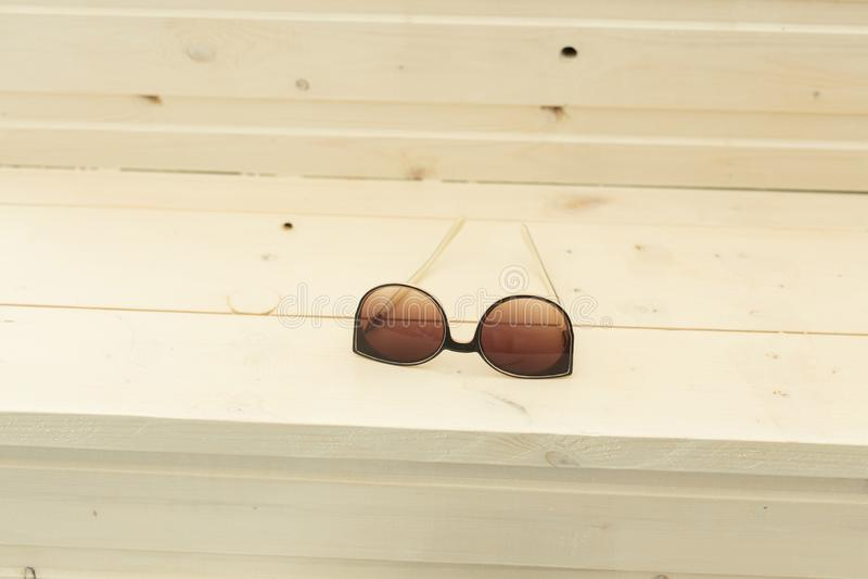 Gafas de sol marrones de la moda que mienten en la tabla de madera fotos de archivo