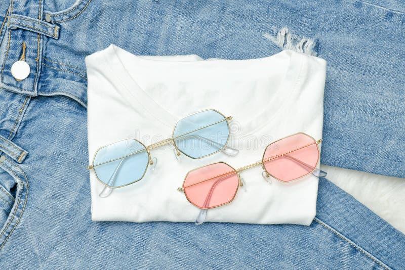 Gafas de sol multicoloras en una camiseta blanca y vaqueros Fashionabl fotos de archivo