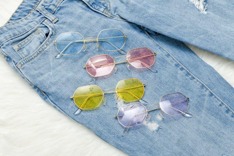 Gafas de sol multicoloras en vaqueros concepto de moda imagen de archivo
