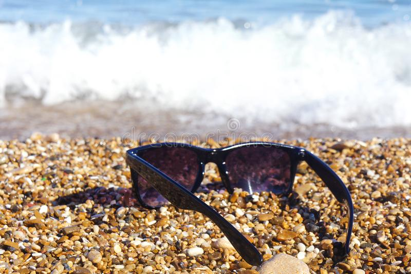 Gafas de sol plásticas contra la perspectiva de piedras del mar Mar en el fondo fotos de archivo