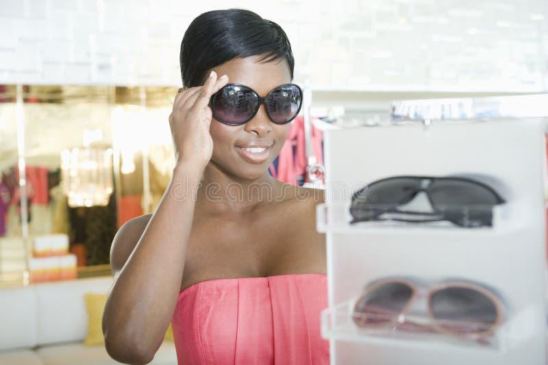 Gafas de sol que intentan de la mujer fotografía de archivo libre de regalías