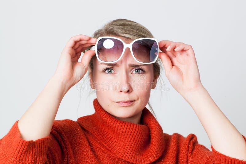 Gafas de sol que intentan del suéter del invierno de la muchacha que llevan infeliz imagen de archivo libre de regalías