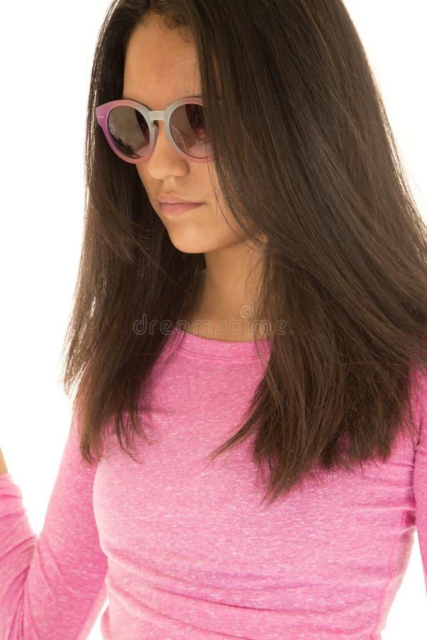 Gafas de sol que llevan de la muchacha adolescente hispánica linda y una blusa rosada imagen de archivo libre de regalías