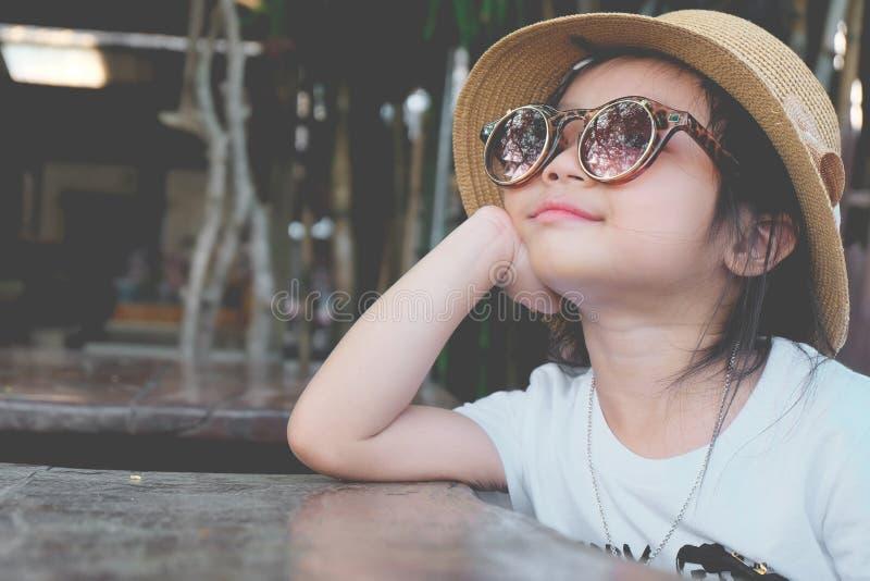 Gafas de sol que llevan de la muchacha asiática linda del niño y un sombrero foto de archivo libre de regalías