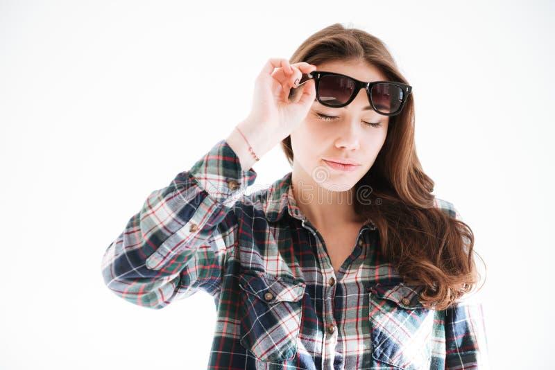 Gafas de sol que llevan de la mujer que se colocan sobre el fondo blanco imagenes de archivo