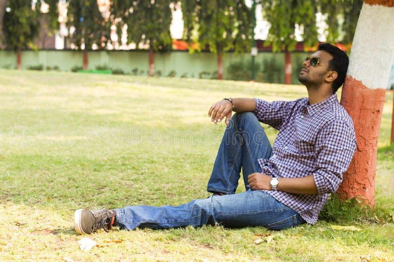 Gafas de sol que llevan del hombre joven que se relajan y que se inclinan contra árbol imagen de archivo libre de regalías