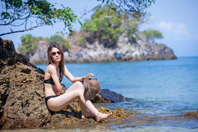 Gafas de sol que llevan de la mujer asiática en el bikini que se relaja en la playa imagenes de archivo