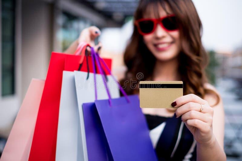 Gafas de sol que llevan de la mujer feliz que presentan con los bolsos de compras y la tarjeta de crédito, concepto que hace comp fotografía de archivo libre de regalías