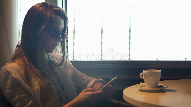 Gafas de sol que llevan de la señora bonita que mandan un SMS en el teléfono en el café, para amigo que espera imagen de archivo