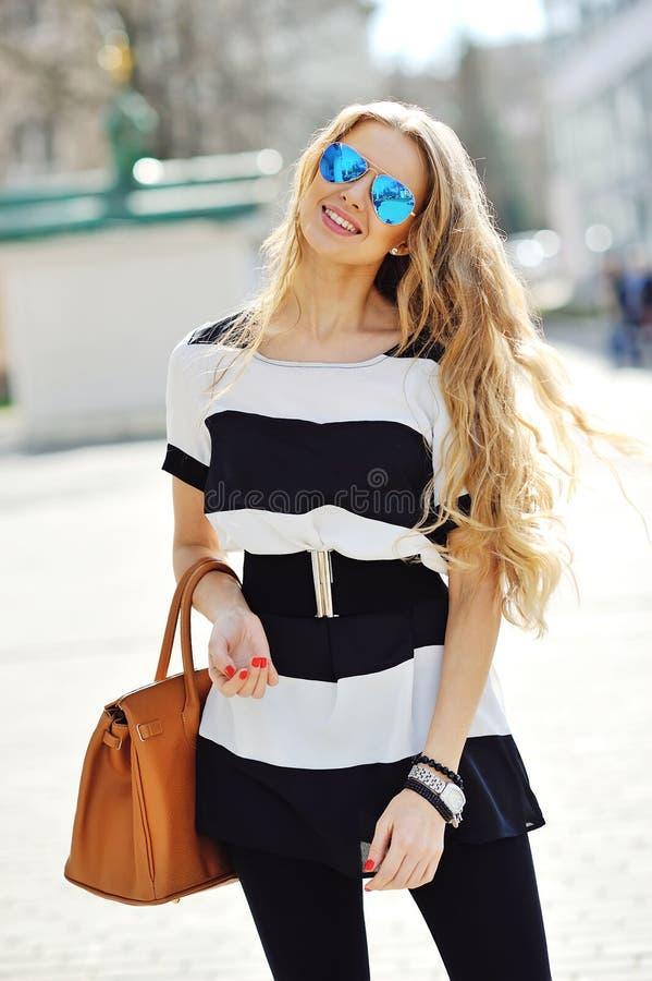 Gafas de sol que llevan rubias hermosas de la mujer joven fotografía de archivo