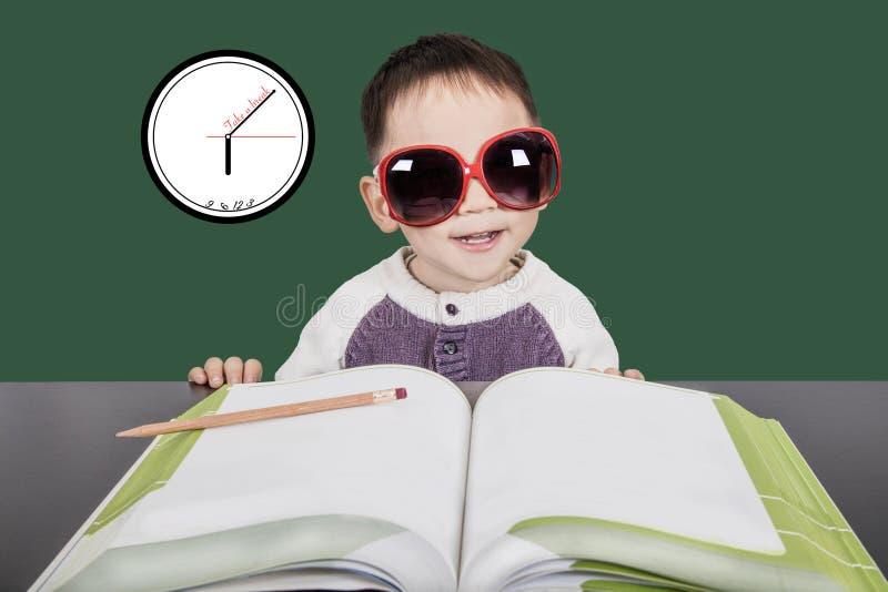 Gafas de sol que llevan y el estudiar del niño elegante imagen de archivo libre de regalías