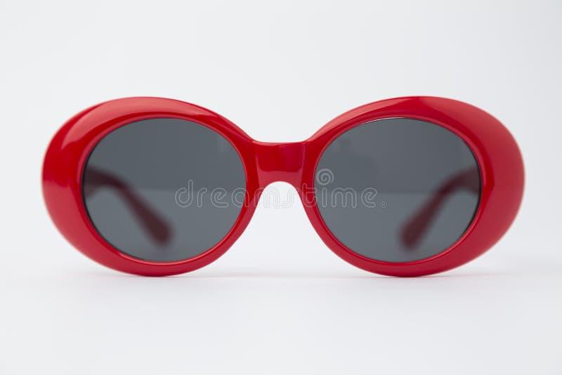 Gafas de sol redondas rojas lindas en el fondo blanco fotografía de archivo