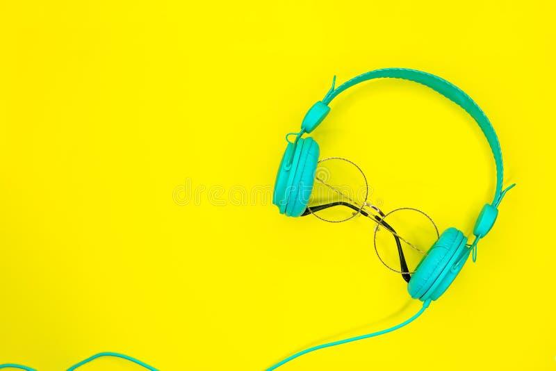 Gafas de sol redondas y auriculares azules en fondo amarillo del verano con el espacio de la copia imágenes de archivo libres de regalías