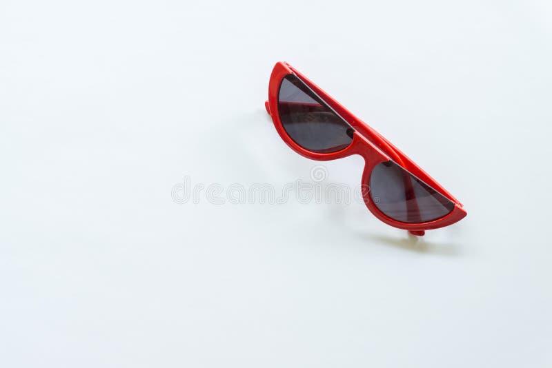 Gafas de sol rojas en el fondo blanco imagenes de archivo