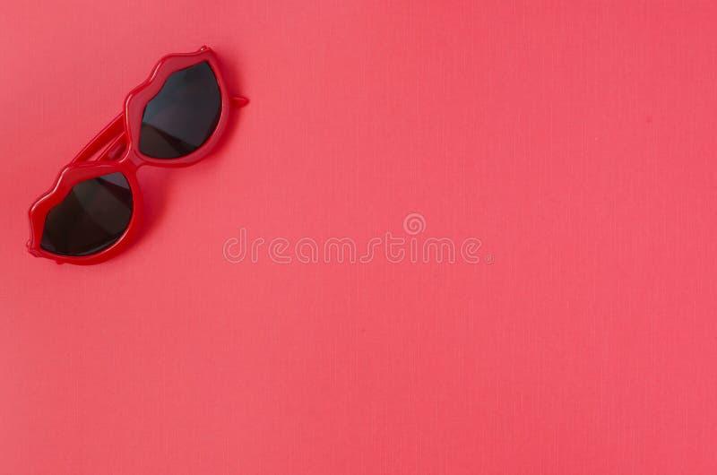 Gafas de sol rojas Fondo rojo imagenes de archivo