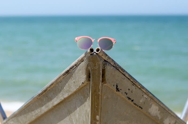 Gafas de sol rosadas contra el sol en un barco cerca del mar fotografía de archivo