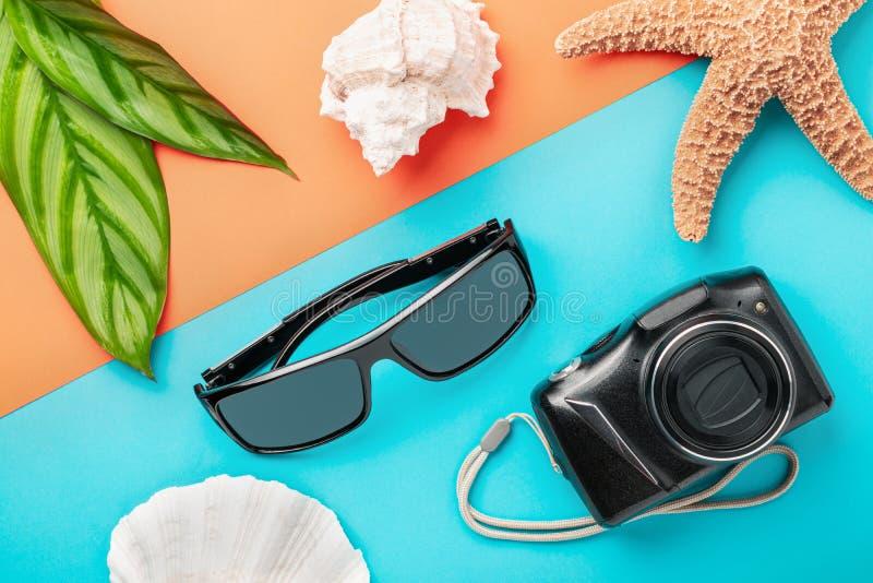 Gafas de sol y cámara digital en fondo del color como concepto de las vacaciones de verano imagenes de archivo