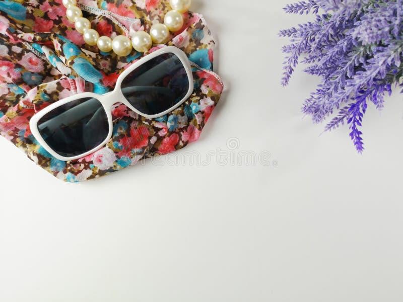 Gafas de sol y collares hechos de perlas, colocado en velos de la moda y flores violetas imagen de archivo libre de regalías