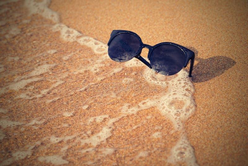Gafas de sol y costa arenosa con la onda imagen de archivo
