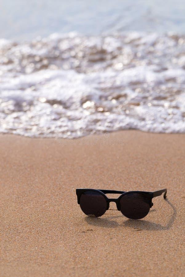 Gafas de sol y costa arenosa con la onda imágenes de archivo libres de regalías