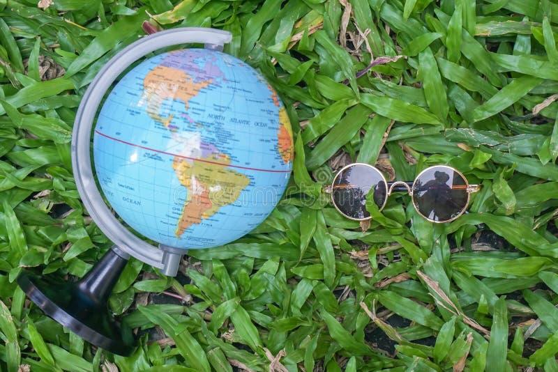 Gafas de sol y globo redondos del vintage del concepto de los días de fiesta para explorar y viajar en yarda verde fotos de archivo