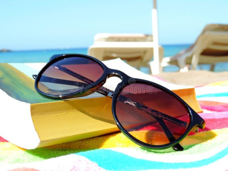 Gafas de sol y libro imagenes de archivo