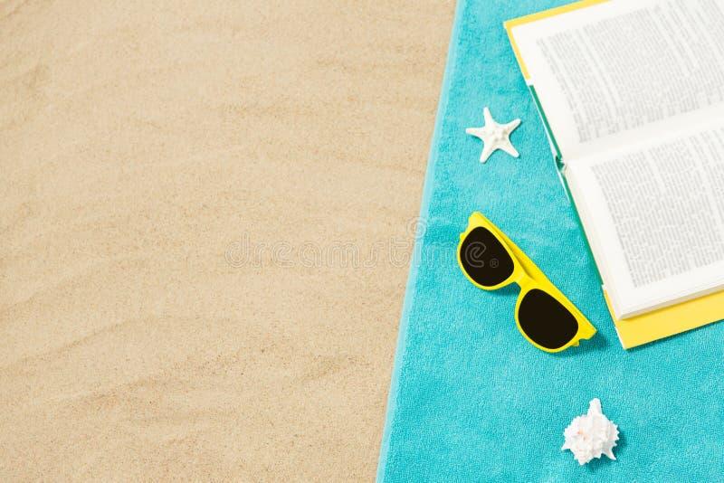 Gafas de sol y libro en la toalla de playa en la arena imagen de archivo