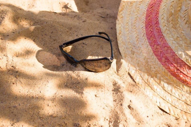 gafas de sol y un sombrero del verano en la arena de la playa Imagen de relajación del concepto de las vacaciones foto de archivo