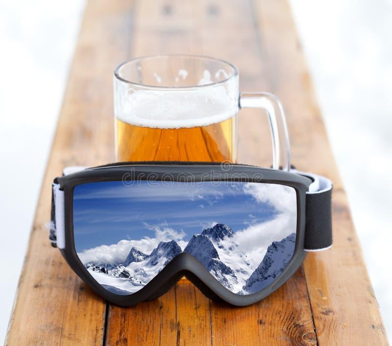 Gafas del esquí con la reflexión de la taza del montaña y de cristal con la cerveza fría fresca foto de archivo libre de regalías