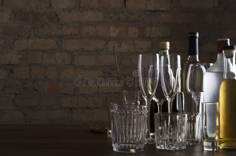 Gafas limpias vacías para vino, champán, cócteles y botellas de bebidas alcohólicas en la mesa contra la pared de ladrillo Noche  fotografía de archivo libre de regalías