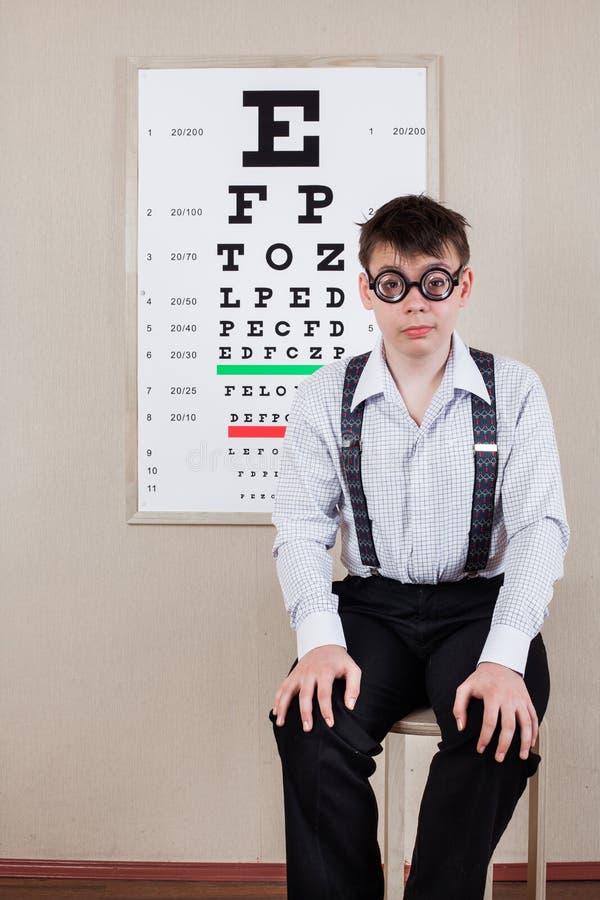 Gafas que llevan de la persona en una oficina en el doctor foto de archivo